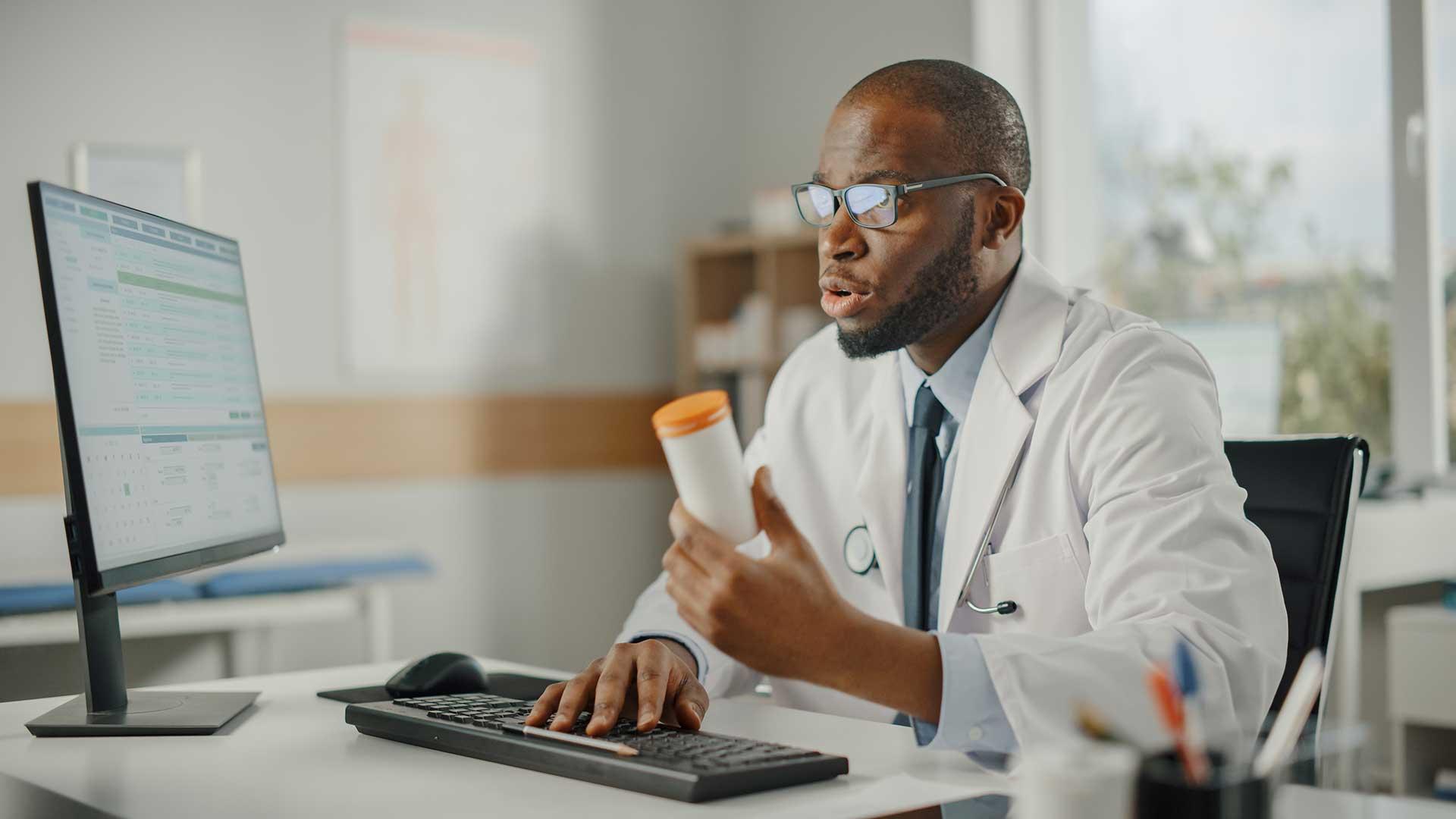 Doctor looking at EHR prescribing new drug to patient